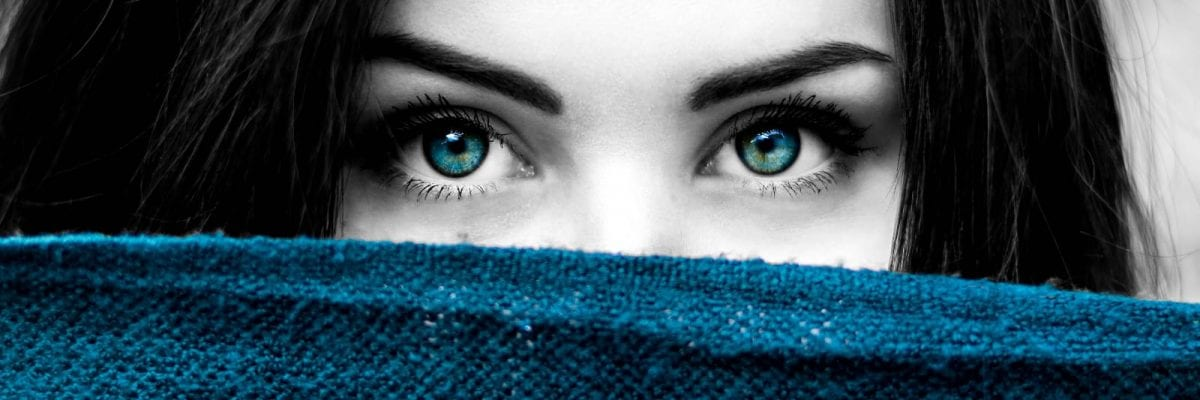 selective-color-of-woman-s-eye-and-blue-textile
